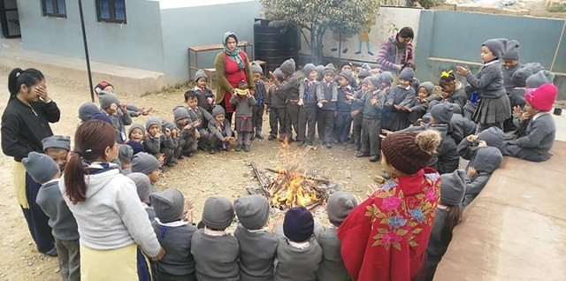 Students studying at Lord Buddha Academy (Tanahu)  burning fire woods in school as the cold increases